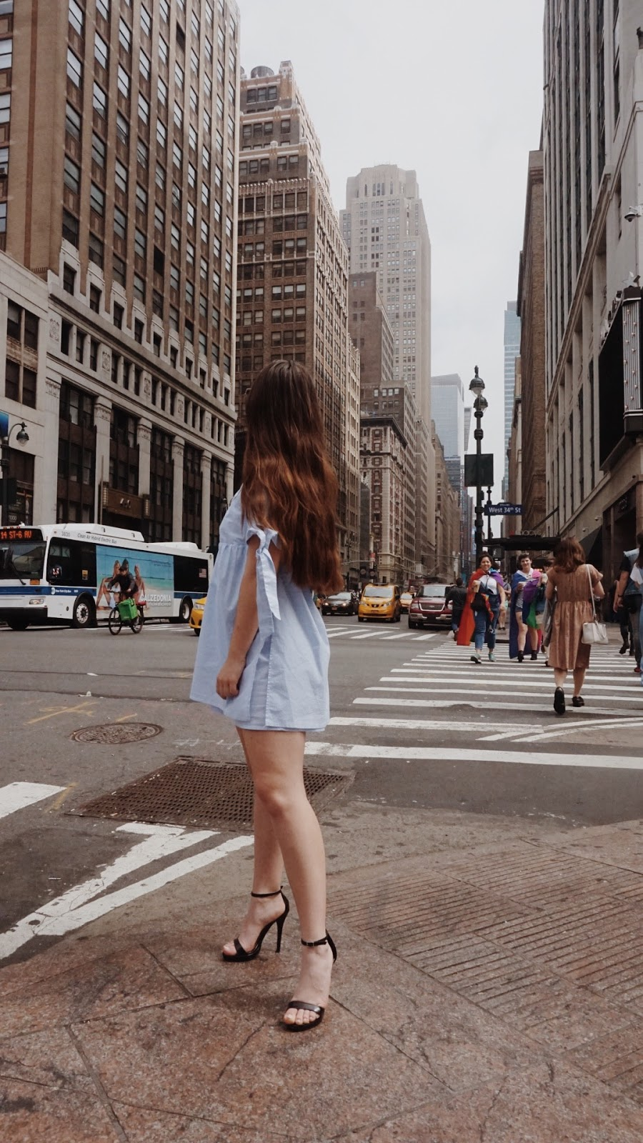girl standing on the street in front of the strewart hotel NYC