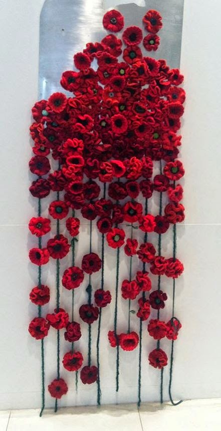 A collection of crocheted and knitted poppies put together as an art installation in my community. Photo used with permission from  Madison Prime.