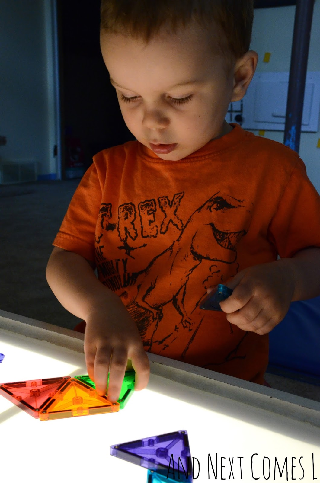 K recreating shapes on the light table using Magna-Tiles from And Next Comes L