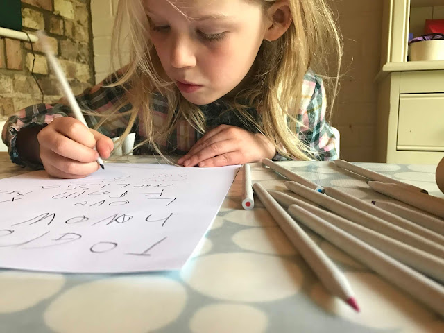 A young child writing with lots of pencils