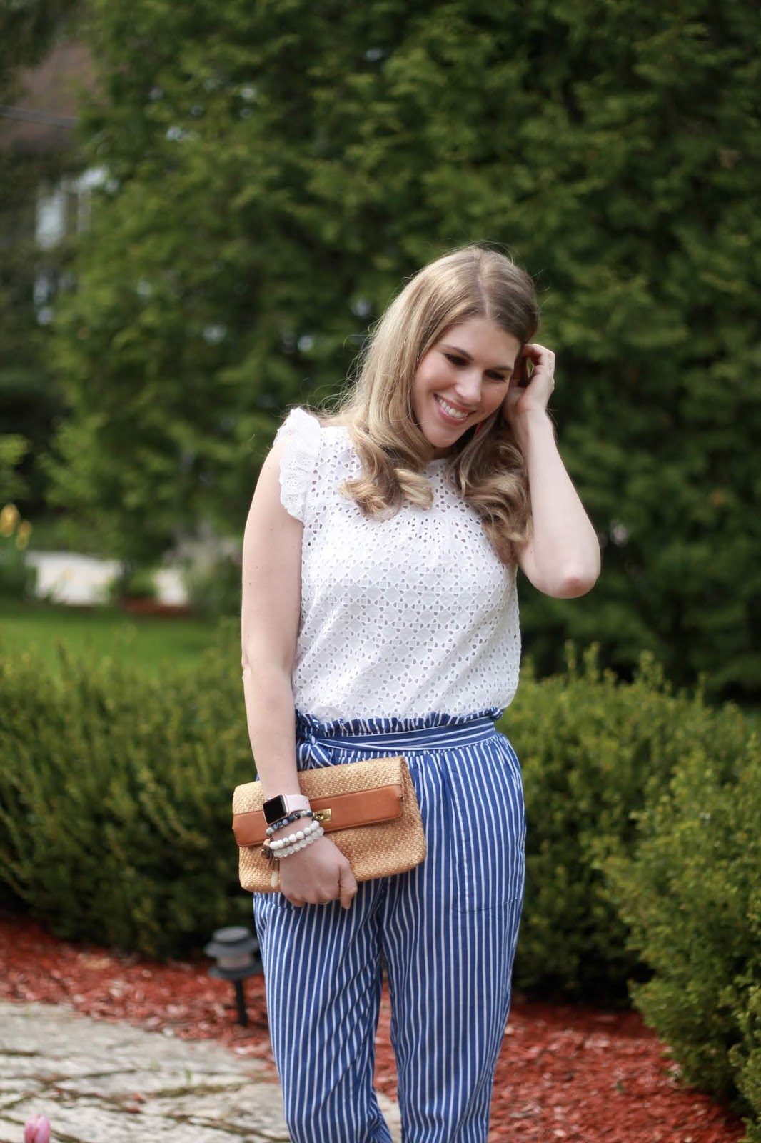 white eyelet top, blue striped paper bag pants, straw clutch, pink pumps