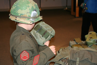 Child trying on military gear at PA Military Museum event