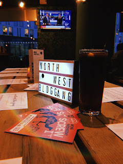 light box saying north west blog gang on a table in a restaurant with a glass of coke