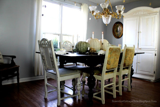 rosevinecottagegirls.com | table in a dining room with grey walls and white armoire set with pumpkins and dry flowers