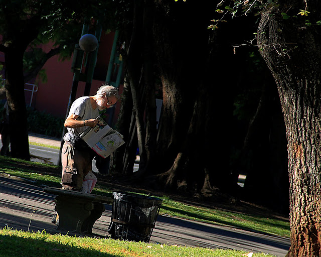 Gente en el pisaje.Hombre leyendo en el parque