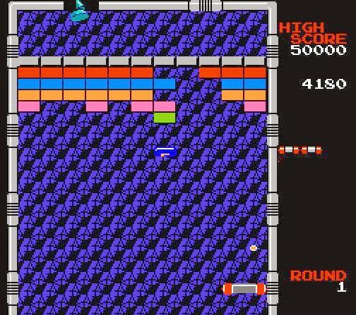Captura de pantalla del videojuego Arkanoid. La imagen muestra la pelolita rebotando contra los ladrillos de colores. Se aprecia también la bajada de un Power Up, azul