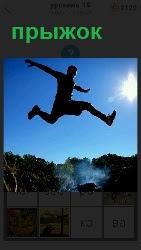 мужчина совершает прыжок через канаву, широко расставив ноги и руки