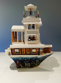 Miniature wooden painted artist's arks on display in a gallery.