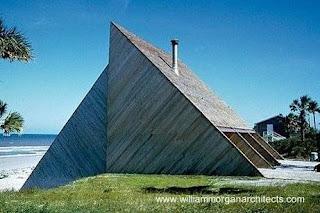 Cabaña de madera de forma geométrica sobre la arena al borde del mar