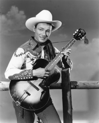 Portrait of Roy Rogers in cowboy hat and holding guitar in front of wooden fence railing