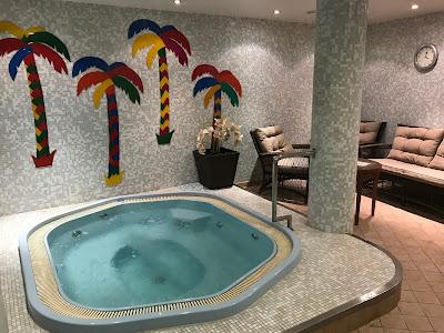 Flislagt rom med boblebad og palmer på veggen.