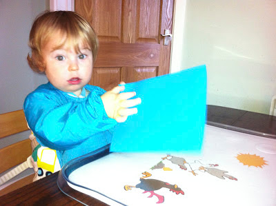 Child with a piece of blue card, ready to create birthday card