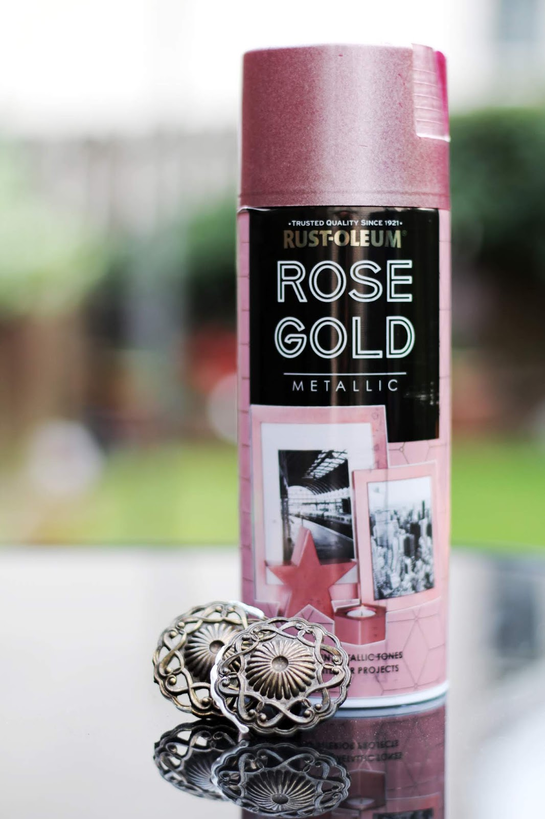 Close up of rose gold spray paint and two old vintage brass drawer handles sitting on a black glass garden table