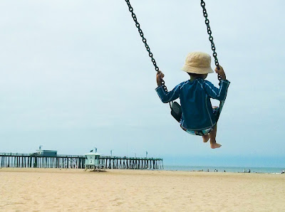 Boy swinging on a swing on a beautiful sandy beach with a pier and ocean in the background
