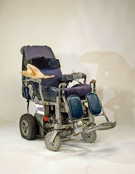 Old-style electric wheelchair, well worn.