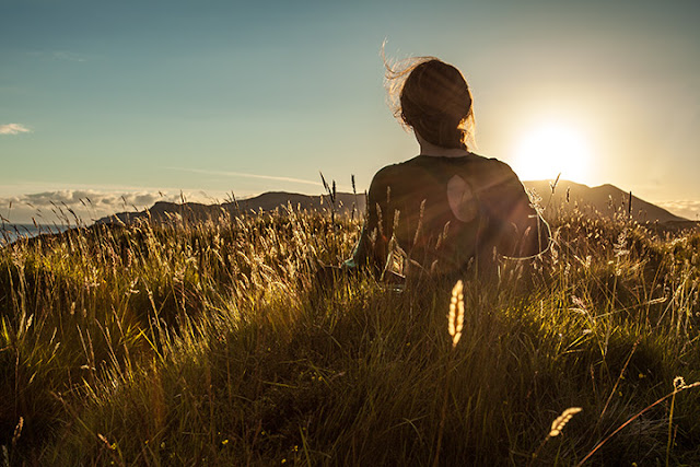 Woman sitting in long grass watching the sun setting