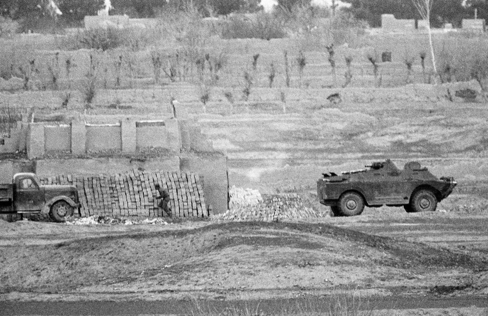 A Soviet soldier runs for cover, as his armored car comes under fire from Muslim rebels, near the town of Herat, on February 13, 1980.