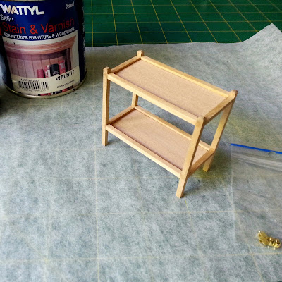 Modern miniature tea trolley on a workbench with a tin of stain and a bag of miniature castors next to it.