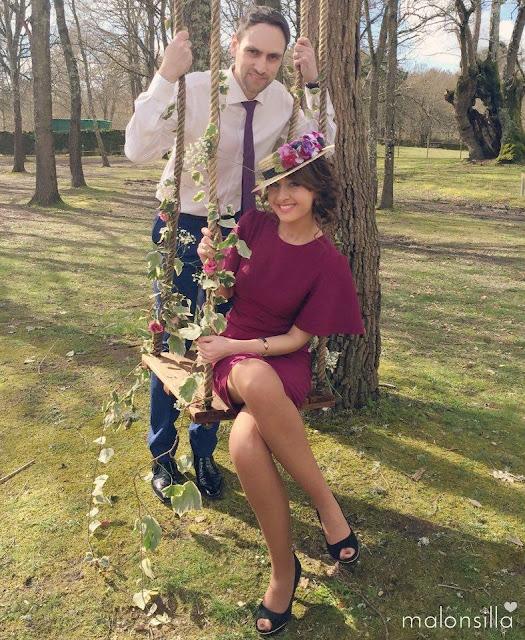 Invitada a boda con vestido berenjena de Asos, escote en la espalda y estola de pelo verde, combinado con canotier Juno y bolso de terciopelo verde, pareja sentada en un balancín / columpio de jardín