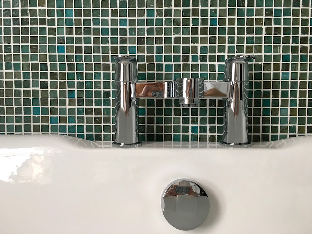 tiled wall and bath taps