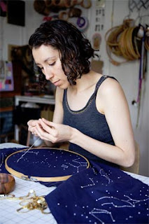 Jessica Marquez stitching a constellation pattern on a dark blue table runner
