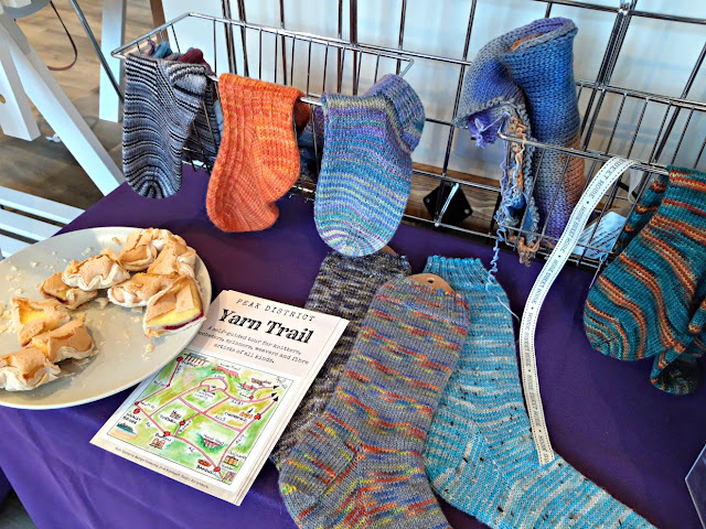 Hand-knitted sock samples in various colours knitted from Peak District Yarns yarn.  To the left of the picture is a plate of Tidza Pud cake