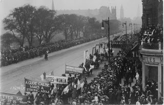 A black and white photograph of a procession of people carrying banners saying, for example, Votes for Women, they are marching diagonally from the top right of the frame to the bottom left and the Edinburgh skyline is visible in the background.