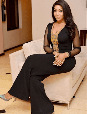 Co-founder of good hair ltd - Kika Osunde sitting is a brown sofa chair wearing a black palazzo dress and a lovely hair flowing to her shoulders
