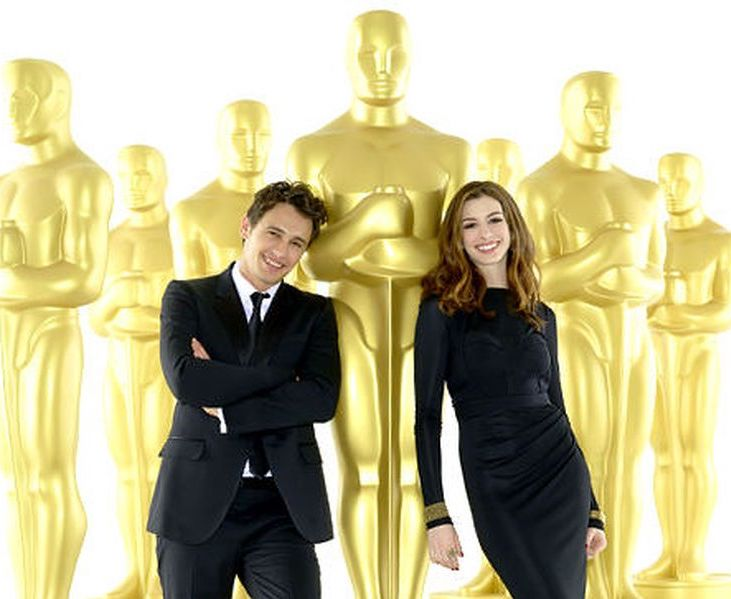 James Franco and Anne Hathaway posing in front of giant replicas of Oscar statuette