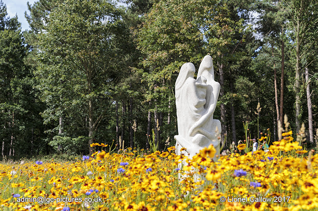 A family life size statue in a sea of wild flowers