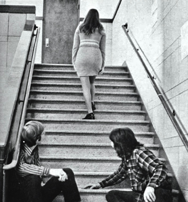 Two teen boys watch a girl walk upstairs in a short skirt. 1960s. Frighten the Horses. marchmatron.com