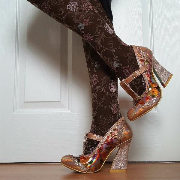 side view of legs wearing brown floral tights and metallic peach shoes with one leg lifted backwards