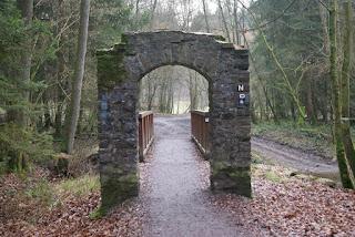 Ein gemauerter Torbogen mit dahinterliegender Brücke führt über die Dhün.