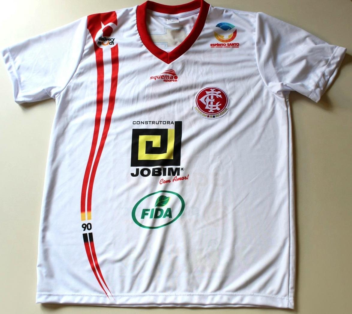 15d18d5446 A camisa reserva é predominantemente vermelha com a cor branca aparecendo  na gola e em listras curvas do lado direito do uniforme. O terceiro ...