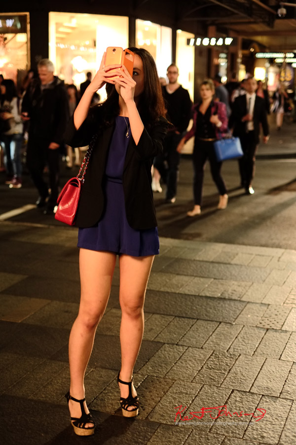 Black strappy heels, navy blue playsuit and black jacket with red cannel handbag, photographing the Vogue sign - VFNO 2013 Pitt Street Mall - VOGUE Fashion Night Out Sydney