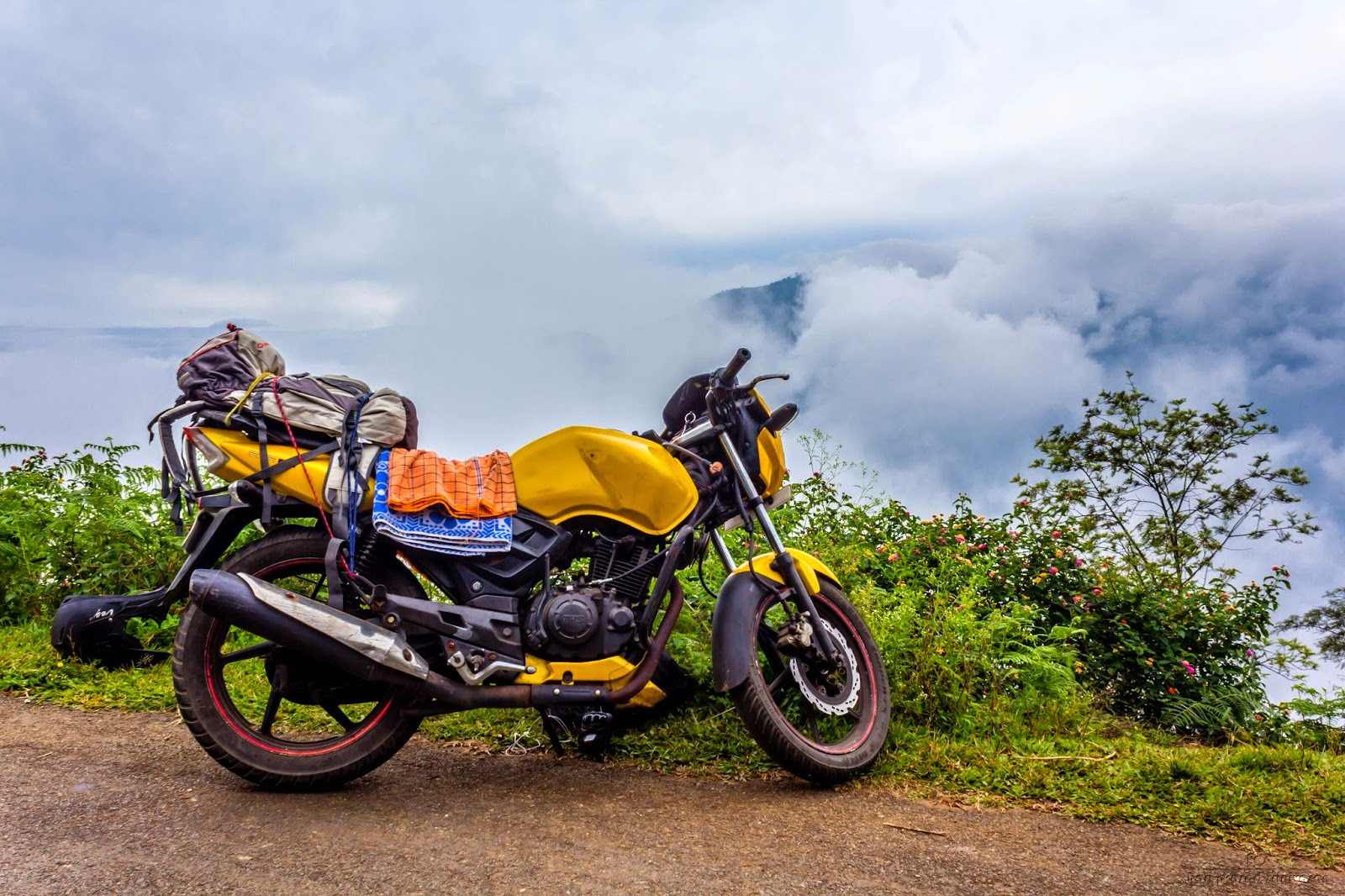Riding above the clouds. Bike in the foreground and a mountain covered in clouds in the background.