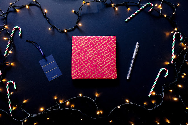 Personalised Christmas wrapping paper, a silver pen and a label