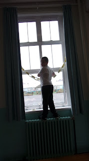 schoolboy standing on radiator in assembly hall