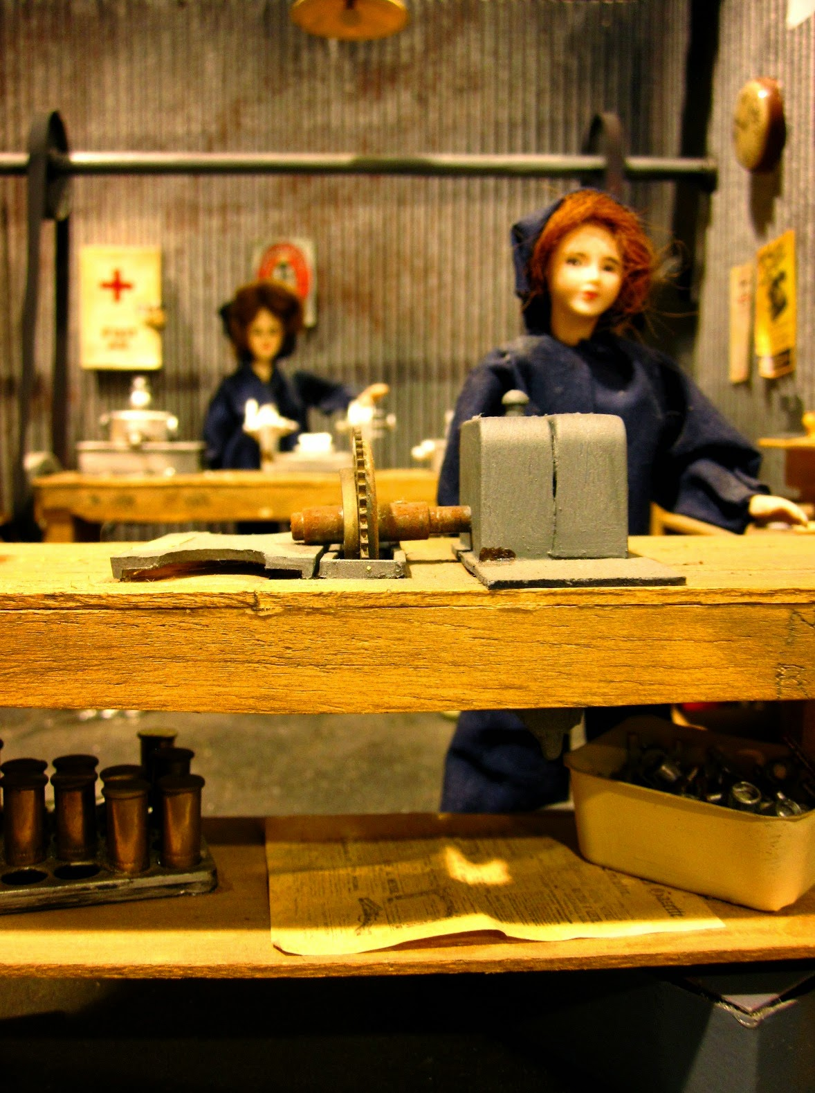 Dolls house miniature of a wartime munitions factory with two dolls at machines.