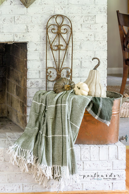 vintage copper boiler with green throw blanket and faux pumpkins on painted white brick fireplace