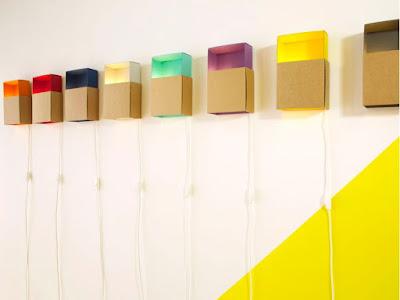 Boîtes à lumière colorées en carton recyclé de la marque ¿adónde? accrochées au mur.