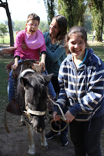Rocío arriba de un pony tan contenta como sorprendida. Al lado su mamá sosteniéndola sonriente y la joven encargada del pony también muy alegre.
