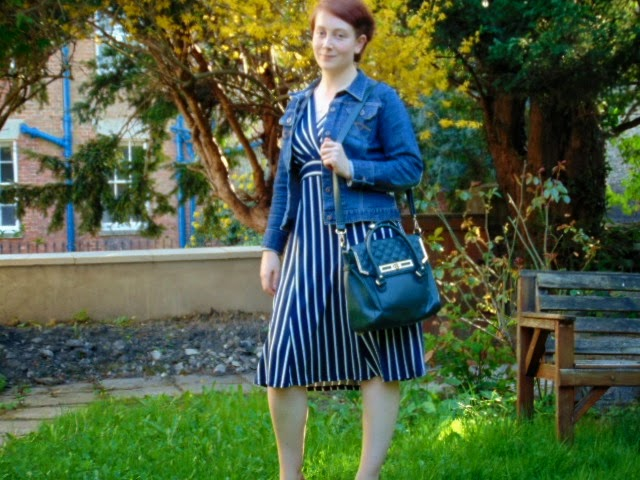 Navy and white-striped dress with denim jacket and green bag