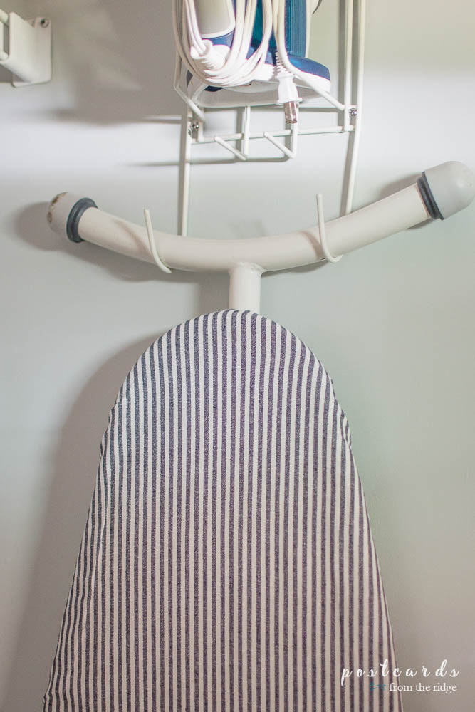 See how she gave her laundry room a cute makeover for less than $100, including this cute ironing board cover!