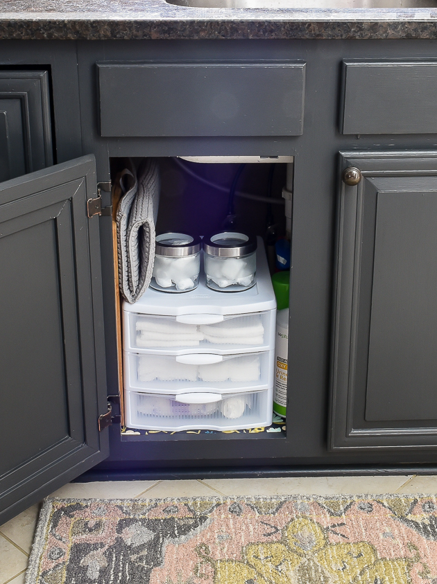 organizing under the kitchen sink with clear storage drawers