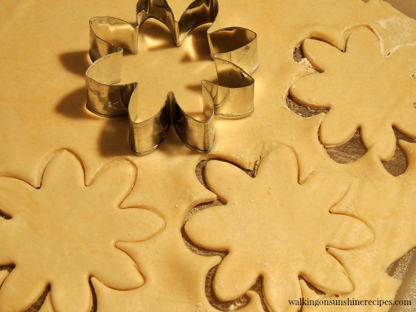 Cutting out Pie Crust into Flower Shapes for Mini Pumpkin Pies from Walking on Sunshine Recipes