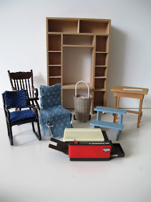 Various one-twelfth scale furniture items, including chairs, a desk unit, a side table, a wicker shopping trolley and a photocopier.