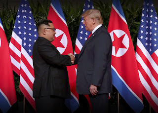 image of USA president Donald Trump and North Korea Supreme Leader Kim Jong Un shaking hands in front of many USA and North Korean flags