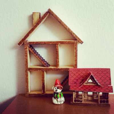 A miniature one-twelfth scale shadow box in the shape of a house displayed behind a tiny dolls house for a dolls house and a Toby dog figurine.