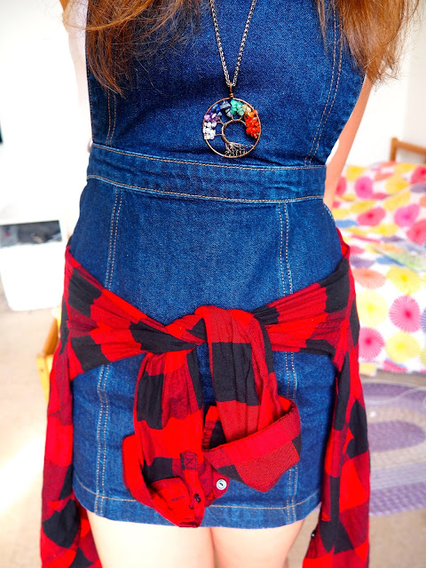 Spring Sunshine - outfit of denim dungaree dress, white top, red & black flannel checked shirt around the waist, and rainbow tree of life pendant necklace